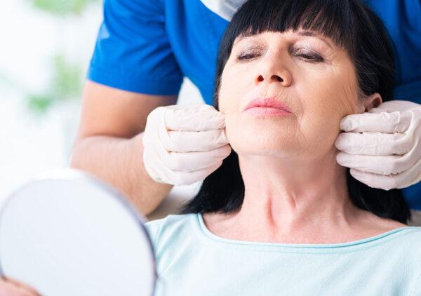 kirurg undersöker kvinna inför kombinationsbehandling av ansikte