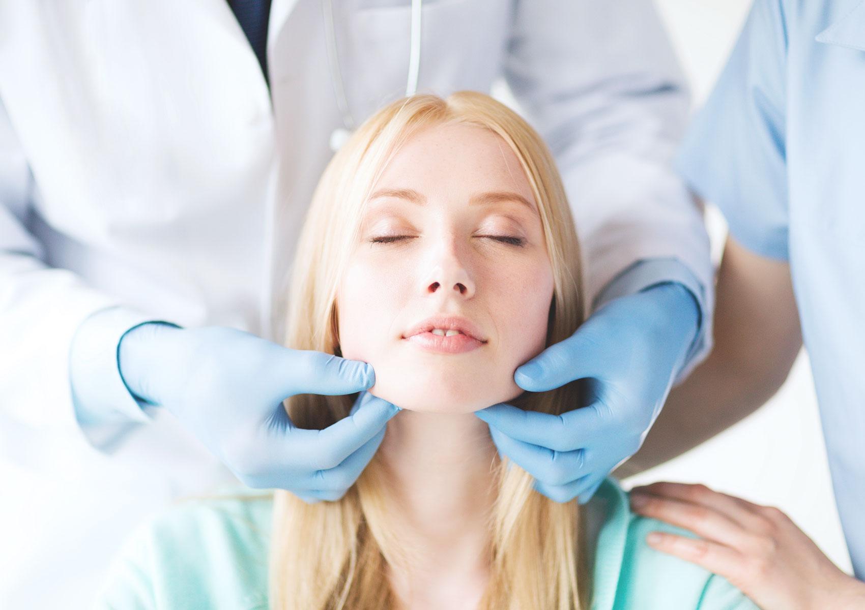 tjej blir undersökt av kirurg innan behandling